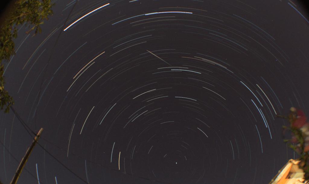 Una perseida en una fotografía de larga exposición mostrando trazos en forma de arco creados por las estrellas debido a la rotación terrestre sobre el sensor fotográfico.